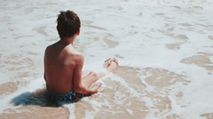 Boy 9 years old sitting on the sand of the sea by the sea. Playing sea sand Stock Footage