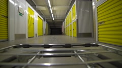 Cargo trolley is moving in the self-storage warehouse. Automatically turns on Stock Footage