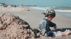 Boy age 2 years old, beautiful appearance, playing in the sand on the seashore Stock Footage