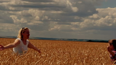 Mother and son running on the wheat field. A happy family Stock Footage