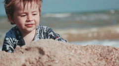 Boy age 2 years old, beautiful appearance, playing in the sand on the seashore - stock footage