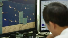 A worker is talking on radio transceiver in the vessel traffic service center Stock Footage