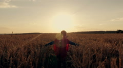 Boy with a superman cape stands in a golden fields Stock Footage