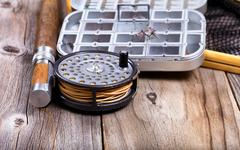 Vintage fly fishing reel and gear on rustic wooden background Stock Photos