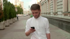Young hansome man walks towards camera and use smartphone business app. Stock Footage