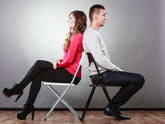 Young couple after quarrel sitting back to back Stock Photos