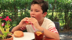 Child in a cafe, eating hamburger Stock Footage