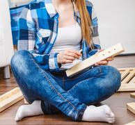 Woman assembling wood furniture. DIY. Stock Photos