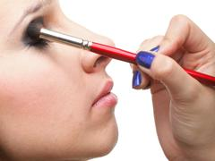 Woman applying eyeshadow makeup brush Stock Photos
