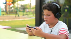 Child listening to music and gaming on the smartphone Stock Footage