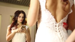 The consultant helps the young woman try a wedding dress. Girl happy to selected Stock Footage
