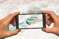 Woman hands with mobile cell phone to take a photo of mineral springs in Turk Stock Photos