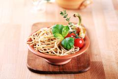 Cooked whole wheat spaghetti in a terracotta bowl Stock Photos