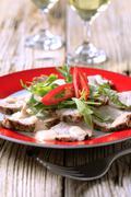 Slices of roast pork tenderloin garnished with salad greens Stock Photos