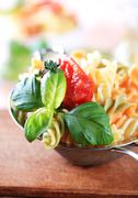 Tricolor corkscrew pasta in a metal sieve Stock Photos