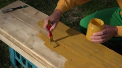 Worker painter hands painting wood surface with paintbrush in yellow color Stock Footage