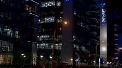 Illuminated Office Buildings In Bussines Center, People Working Late, Tilt Stock Footage