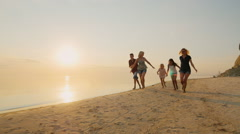 Group of carefree children of different ages and adults have fun running on the Stock Footage