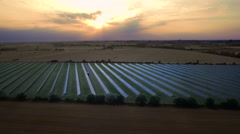 Solar farm in the sunset. Aerial pan shot Stock Footage