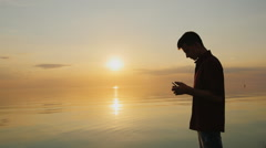 A teenager of 15 years enjoys the phone. It should at sunset on the background Stock Footage