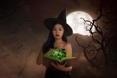 Asian wizard woman holding spell book Stock Photos