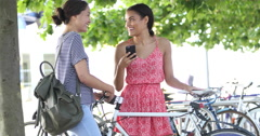 Young female friends socialising outdoors with bicycles Stock Footage