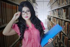 Pretty college student in library aisle Stock Photos