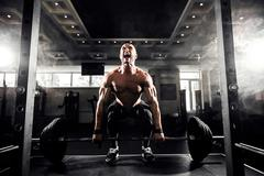 Young shirtless man doing deadlift exercise at gym. Screaming for motivation Stock Photos