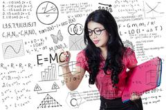 Teacher writes maths and science formula Stock Photos