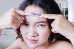 Teenage girl squeeze acne - stock photo