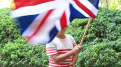 Little boy smiling and waving England flag outside Stock Footage