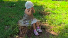 Little girl sitting on a stump and crying Stock Footage