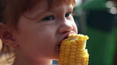 A young girl eats corn off of the cob Stock Footage