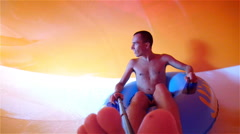 Funny excited young man enjoying summer vacation in water park riding yellow Stock Footage