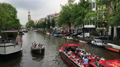 Canal cruise and a small boat in Amsterdam Stock Footage