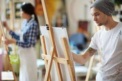 Male artist dressed in beanie hat and white shirt covered in colorful paint sket Stock Photos