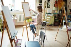 Side view of elegant young female sketching on canvas with pencil in brightly li Stock Photos