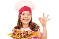 Happy little girl cook with tacos fast food and ok hand sign Stock Photos