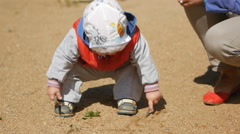 One year old kid playing with sand on the playground. Near the mother helps him Stock Footage
