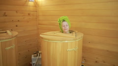 Girl in wooden barrels for spa treatments. anti-aging treatments Stock Footage