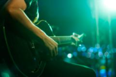 Guitarist on stage for background, soft and blur concept Stock Photos