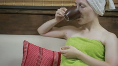Woman on the sofa drinking some tea with shower towel Stock Footage