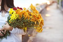 Woman with bouquet flowers vibrant in hands on street sunset background Stock Photos