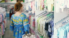 Clothes shopping in baby and maternity shop woman looking for summer dress and Stock Footage