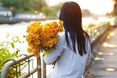 Abstract woman with bouquet flowers vibrant in hands near canal in sunset Stock Photos