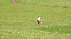 Young woman and little girls on green fields. Stock Footage