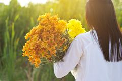 Abstract woman with bouquet flowers vibrant in hands on grass field sunset Stock Photos