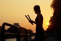 Woman with nunchaku in hands silhouette in sunset, martial arts Stock Photos