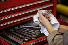 Mechanic wiping her hand with handkerchief Stock Photos