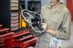 Female mechanic holding spare parts Stock Photos